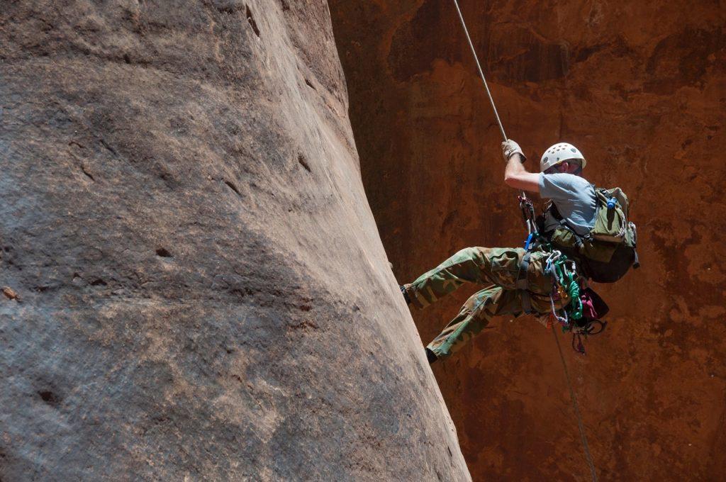 Une homme descendant d'un rocher avec un corde d'escalade